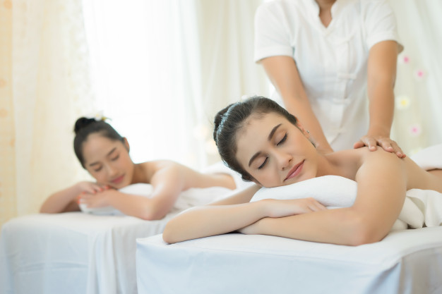 two-cute-young-women-enjoy-relaxing-during-massage-at-spa_1150-3079